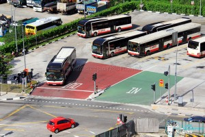 Color-coded terminal entrance shows buses entering from the right side, running against the standard right-hand-drive traffic flow