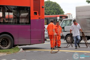 Tow chains are prepared for the towing of the bus